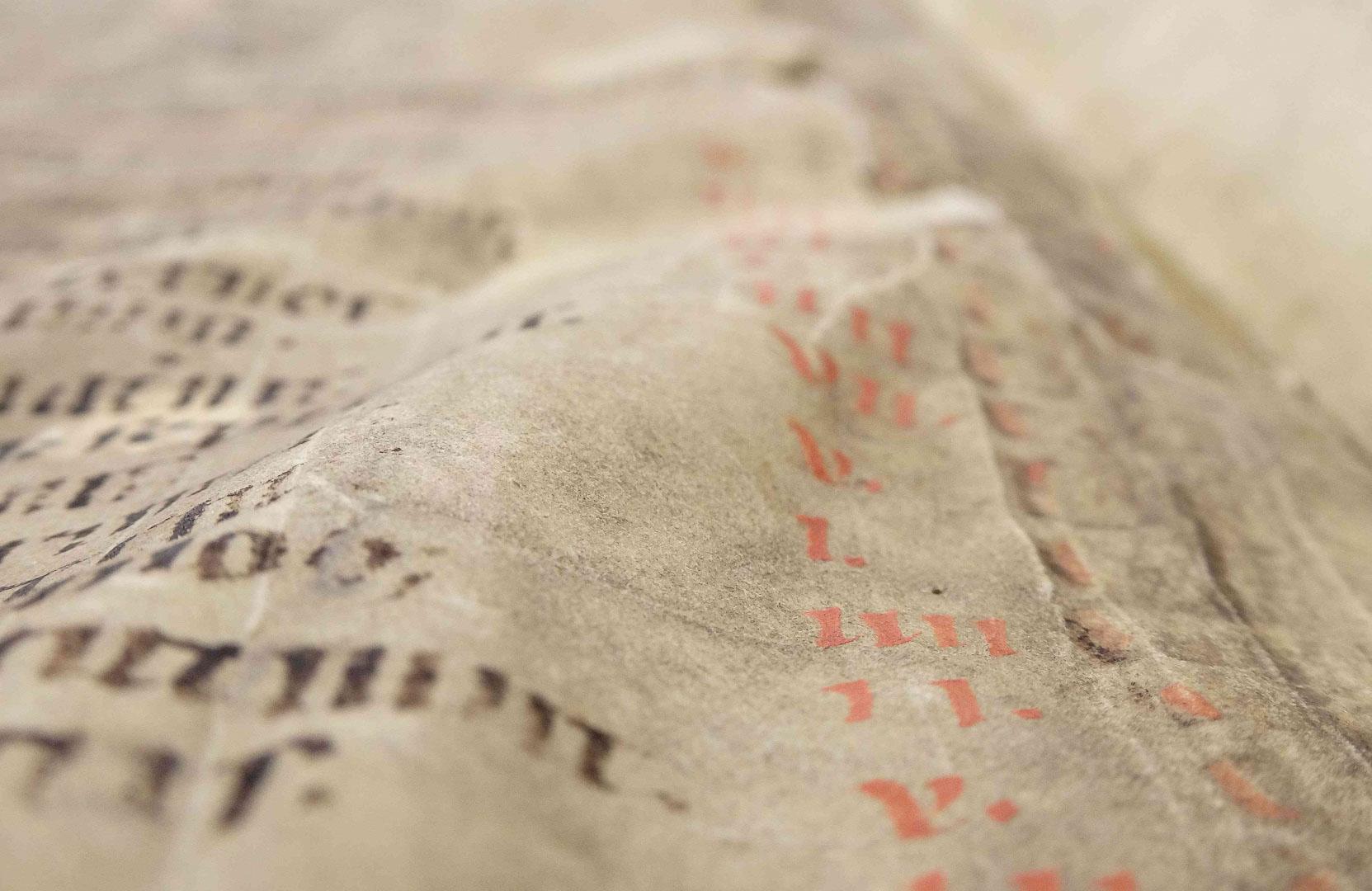Viele Verklebungen und Feuchtigkeit haben das Pergament wellig werden lassen.
