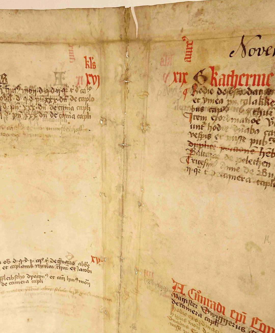 Links und rechts der Lagenmitte sieht man jeweils zwei kleine Schnitte dicht nebeneinander. Durch diese wurden die Pergamentriemchen gezogen, um den Buchblock mit der Buchdecke zu verbinden. Auch der ehemalige Einschlag oben ist deutlich sichtbar.