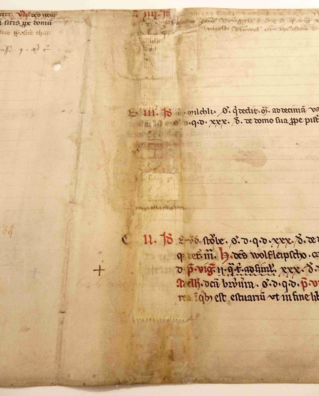 Man sieht deutlich den ehemaligen Buchrücken, mit der hellen Stelle des einstigen Signaturschildes. 4 Bünde, quer zum Rücken, sind durch die vielen kleinen Heftlöcher sichtbar. Das Einbandpergament wurde dort mit dem Buchrücken verbunden.